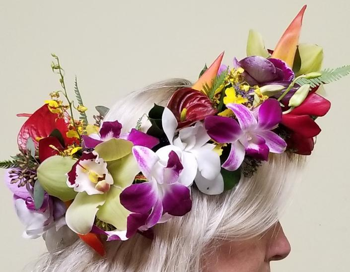 A mix of tropical flowers creates this colorful floral crown; including Cymbidium, Oncidium and Dendrobium orchids, Red anthurium and Heliconia.