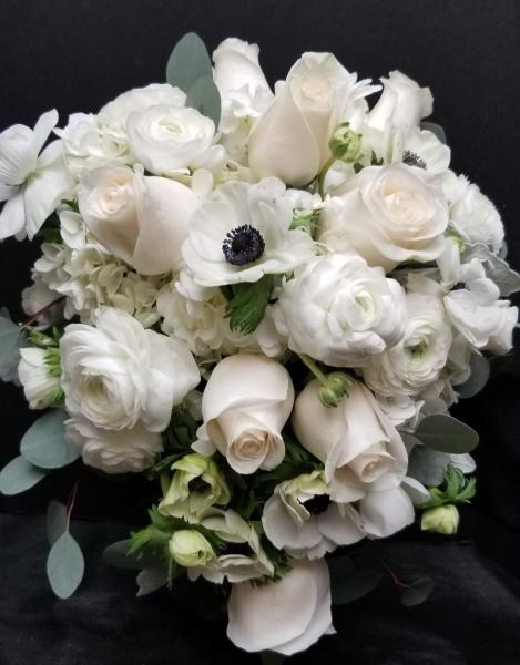 [Image: Hand-Tied bouquet of roses, anemones, ranunculus and hydrangea all in white. Accented with Silver Dollar Eucalyptus]