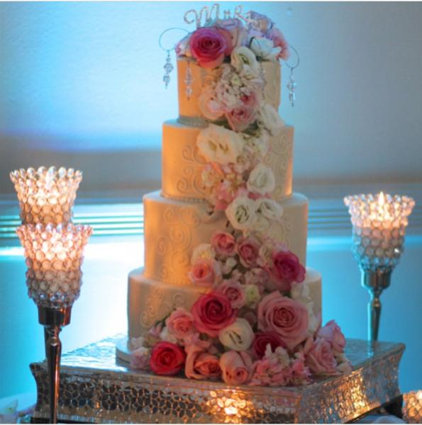 Gorgeously lit and cascading with beautiful roses and hydrangeas in shades of pink and whites, accented with jewels; this cake display steals the spotlight.