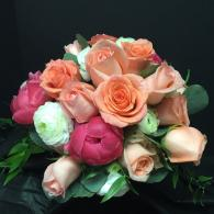Hot pink Peonies, orange roses and white ranunculus give this bridal bouquet a tropical feel.