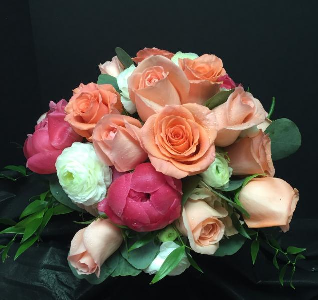 [Image: Hot pink Peonies, orange roses and white ranunculus give this bridal bouquet a tropical feel.]