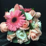 Hot pink Peonies, orange roses, and white ranunculus give this bridal bouquet a tropical feel.