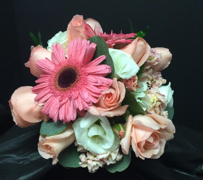 [Image: Hot pink Peonies, orange roses, and white ranunculus give this bridal bouquet a tropical feel.]